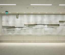 A view of Near Distance, a public art installation in the NEW SLC airport made of white plaster panels with balck charcoal streaks. Gaps between the panels are visible in the center of the rectangular form.