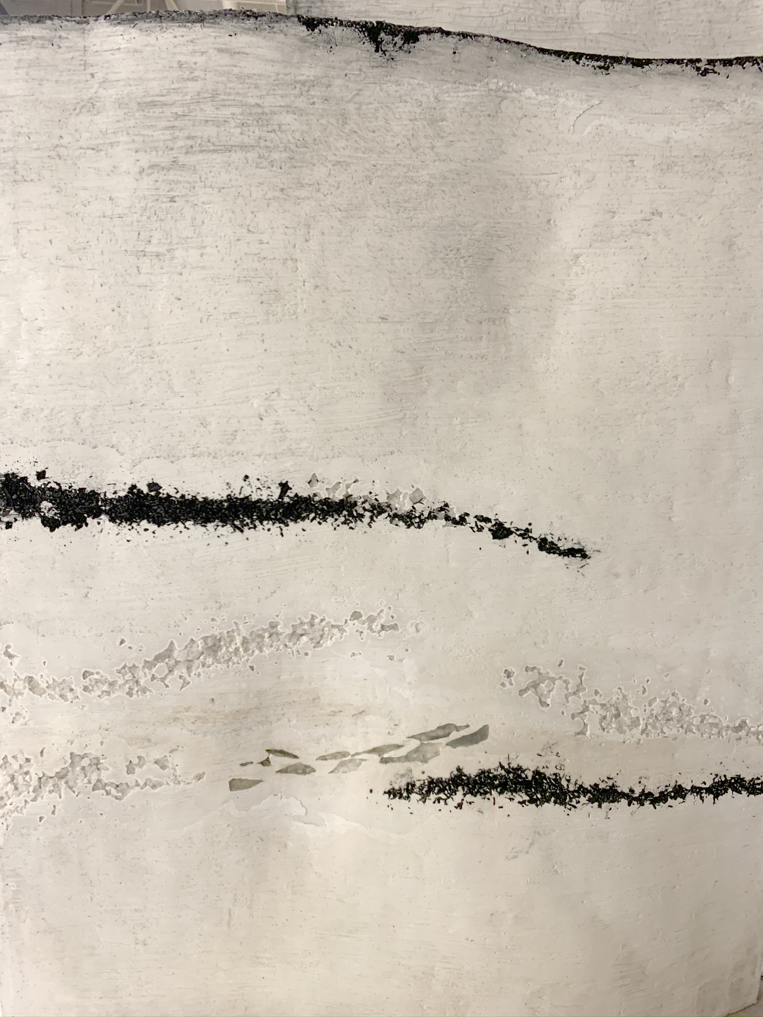 A close up of a white plaster panel with balck charcoal streaks embedded