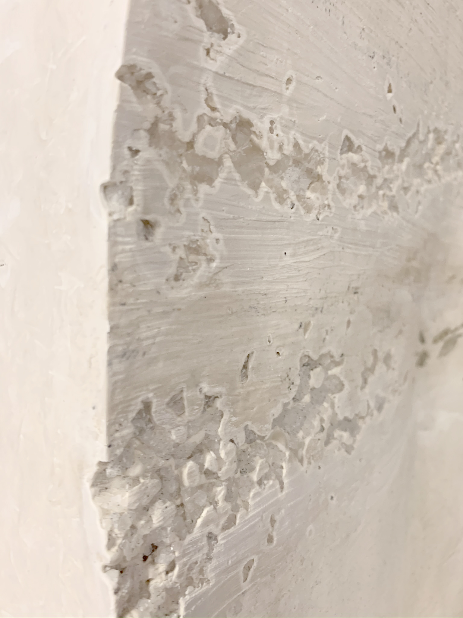 A close up of a white plaster panels with salt crystals embedded
